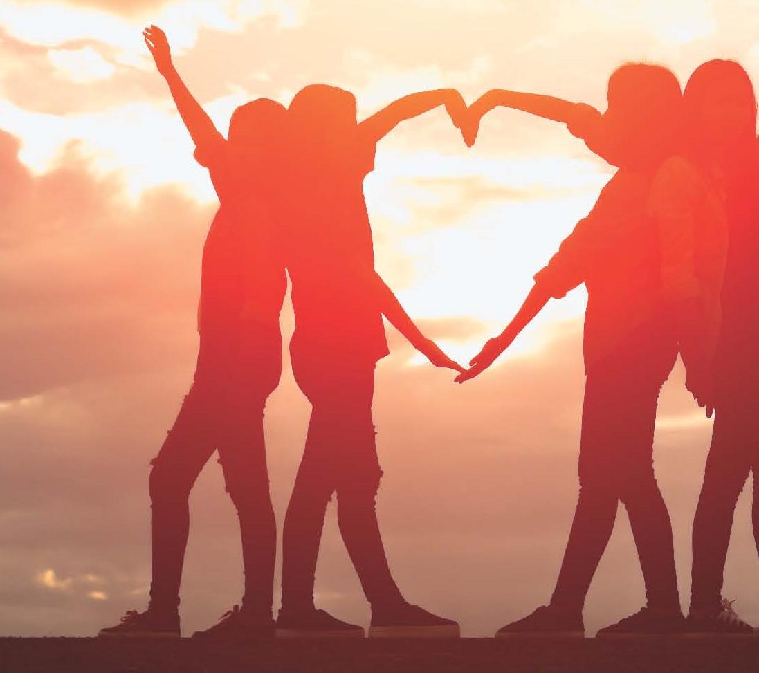 vier Jugendliche formen als Gruppe ein Herz vor dem Sonnenuntergang