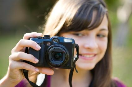 Mädchen hält Fotoapparat vor ihr Gesicht