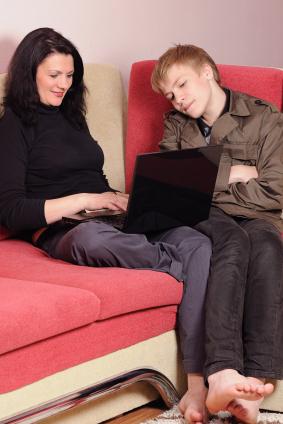 Mutter und Sohn sitzen mit Laptop auf Couch
