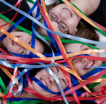 Jugendliche Köpfe unter einem Vorhang bunter Bänder