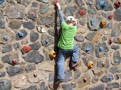 Kind klettert eine Wand hoch